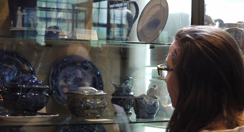 Student looks closely at a ceramics collection