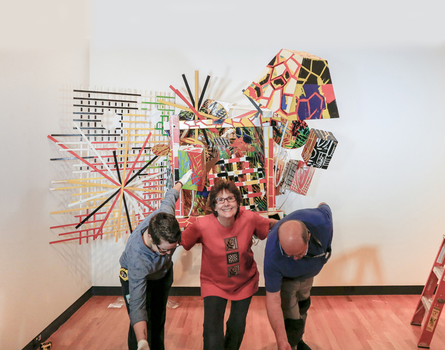 Bob Riddle, Jacqueline Finnegan, and Linda Best take a bow after completing the installation of a Judy Pfaff sculpture