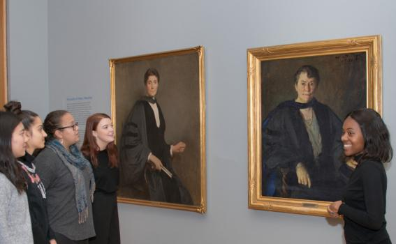 Student tour guides discuss portraits of Mary Woolley