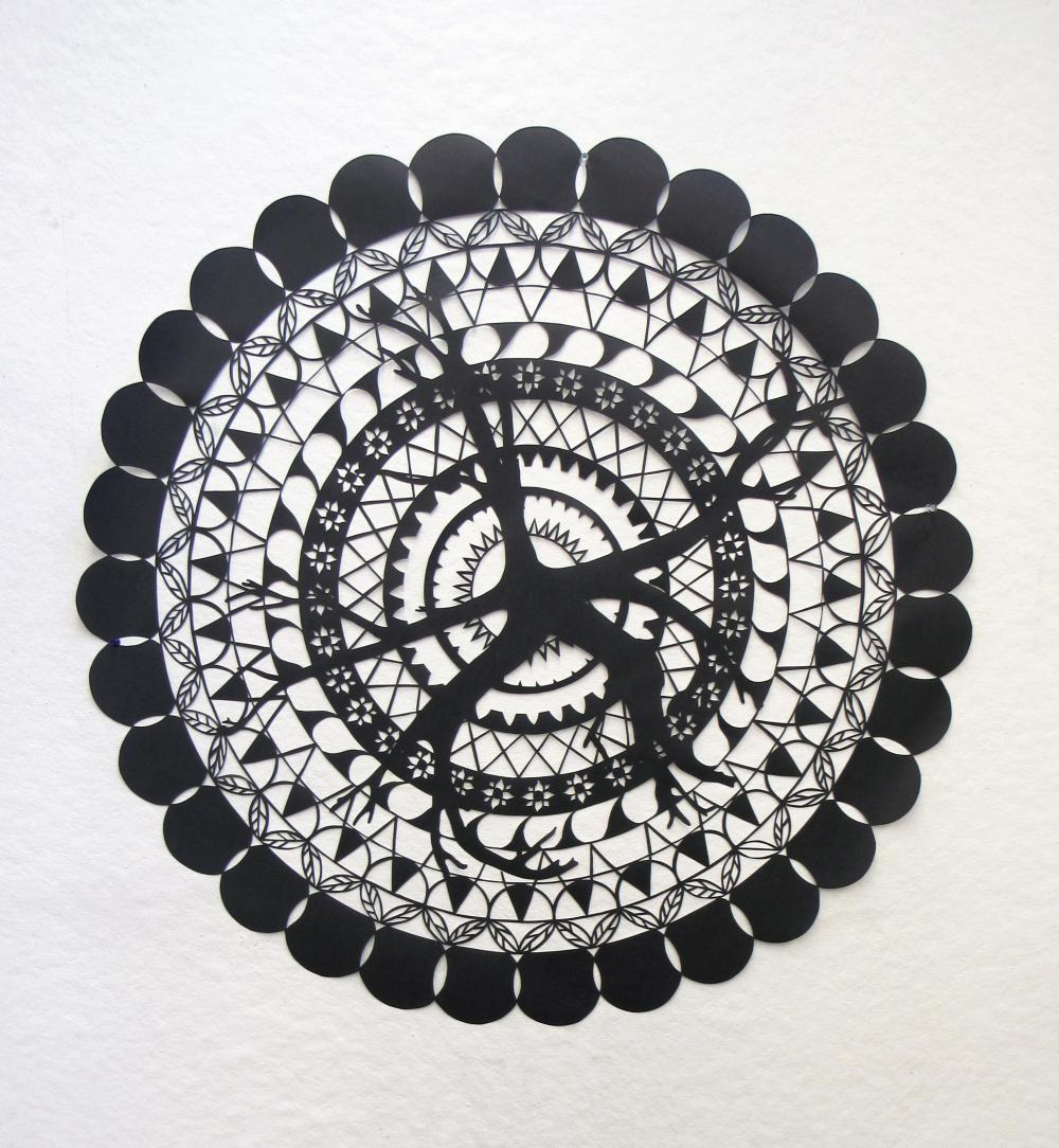 "Mandala made up of leaf, branch, and various decorative patterns cut out of black paper.  The circle measures 3' 2"" in diameter."