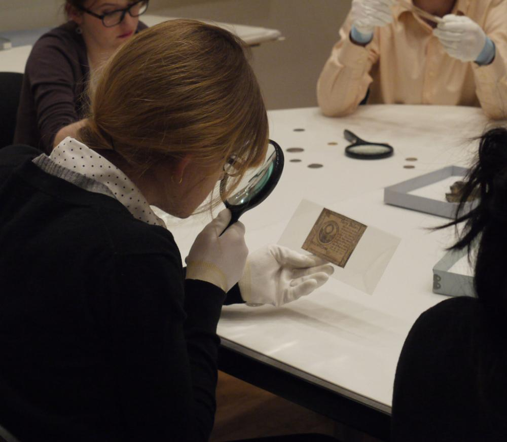 Students examine various forms of money from the Art Museum and Skinner Museum collections