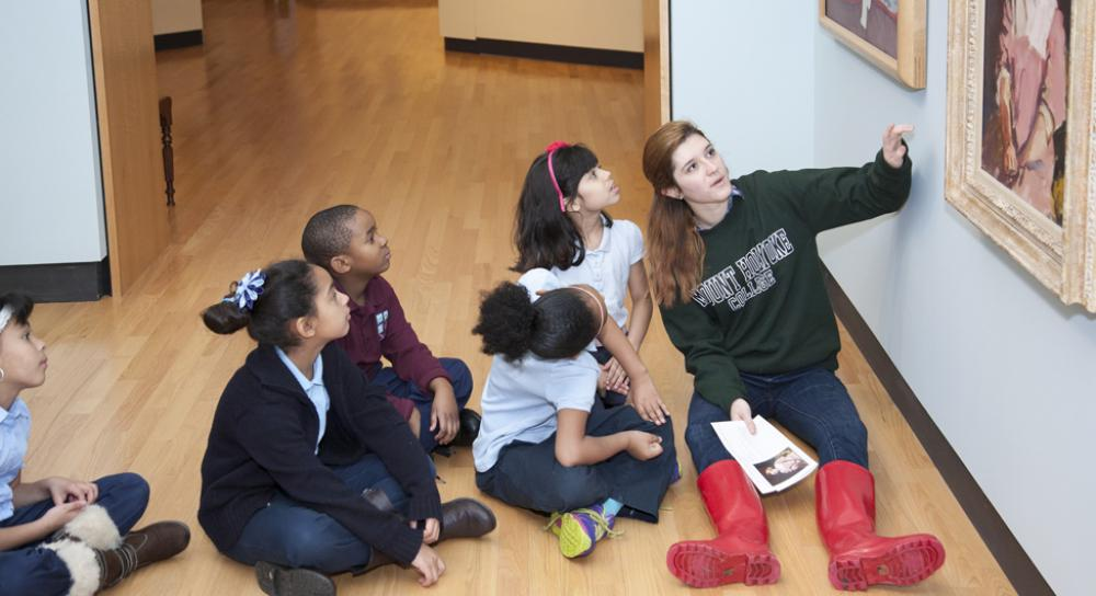 Mount Holyoke student volunteer guides a close-looking activity with elementary students