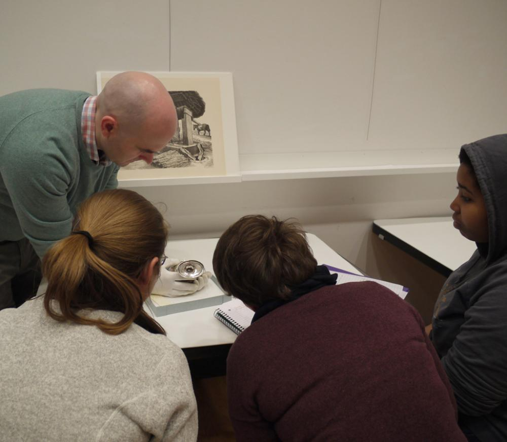 Assistant Curator Aaron Miller shows students a silver vessel