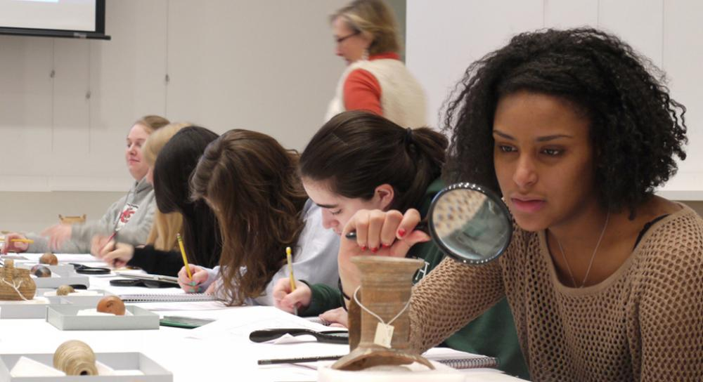 Students look closely at ancient ceramics in the Carson Teaching Gallery