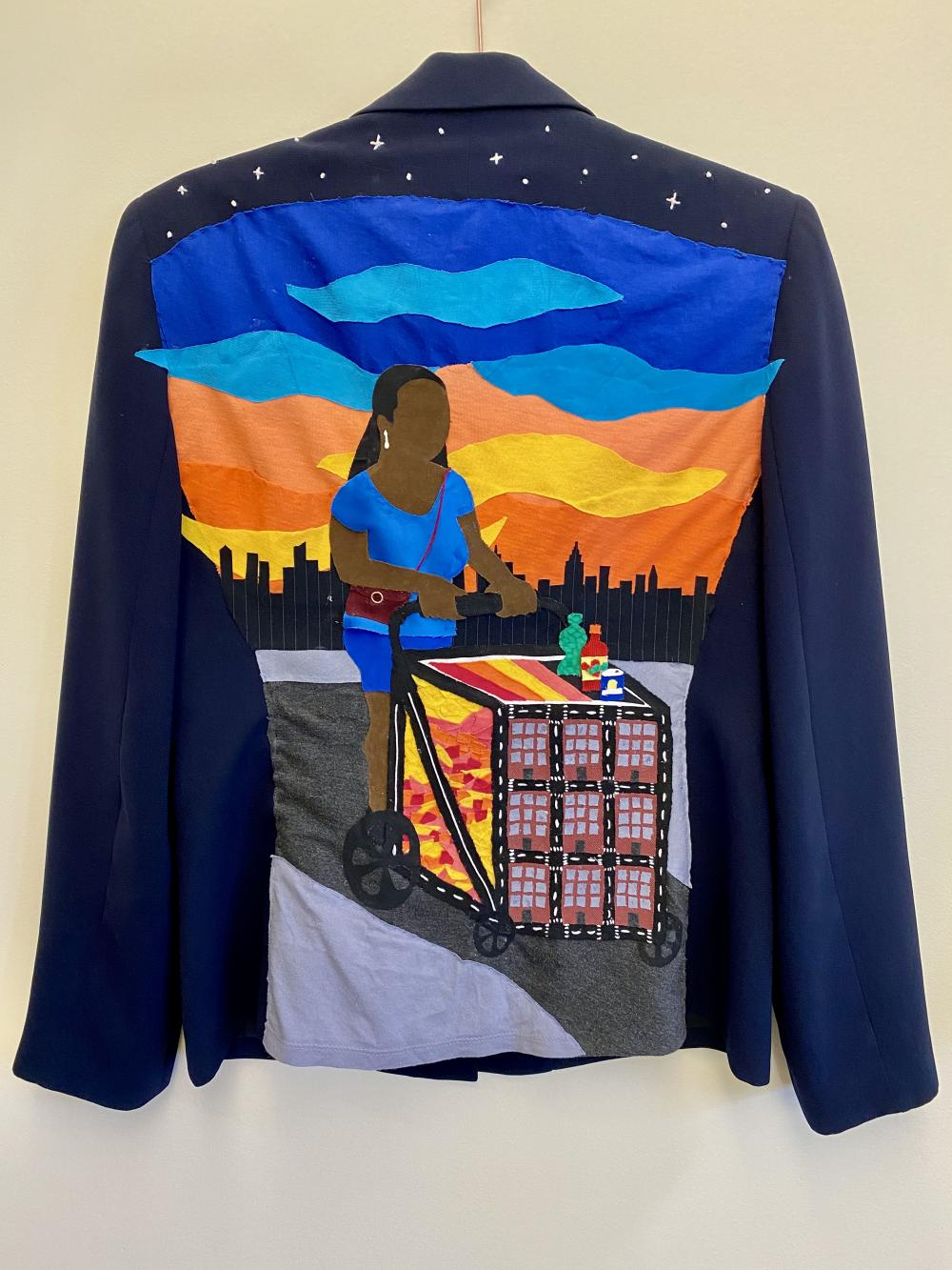 The back of a navy blazer with a sunrise and cityscape background. A woman pushing a fruit cart in the foreground.