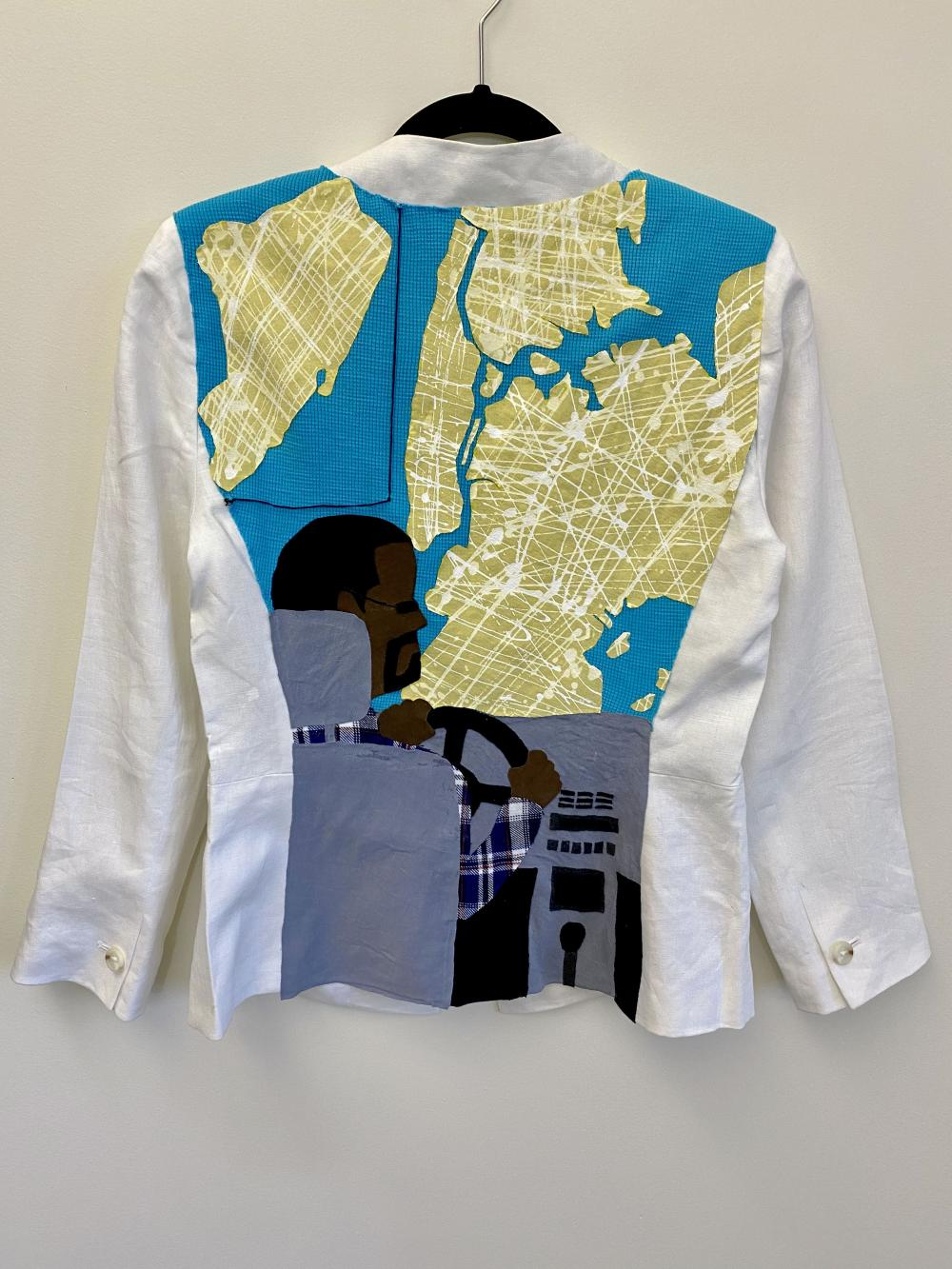 The back of a white blazer with a man driving a car looking out to a map of New York City.