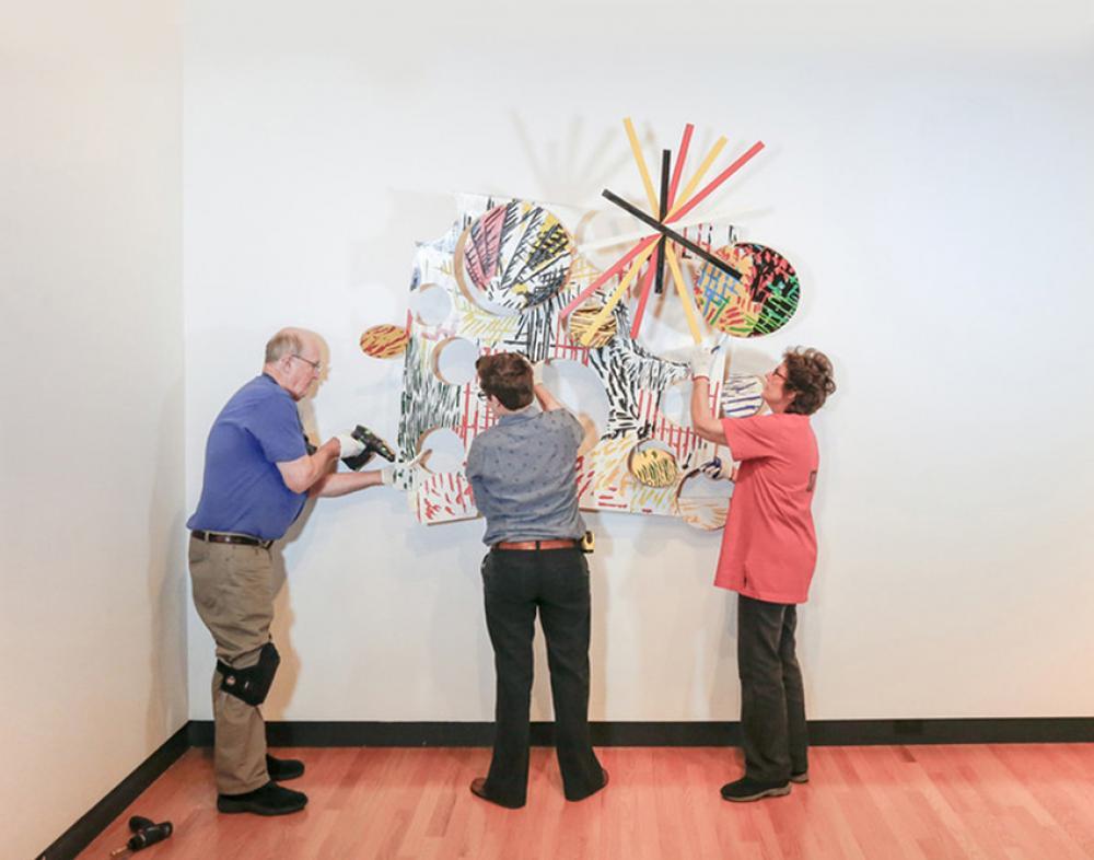Bob Riddle, Jacqueline Finnegan, and Linda Best install a Judy Pfaff sculpture