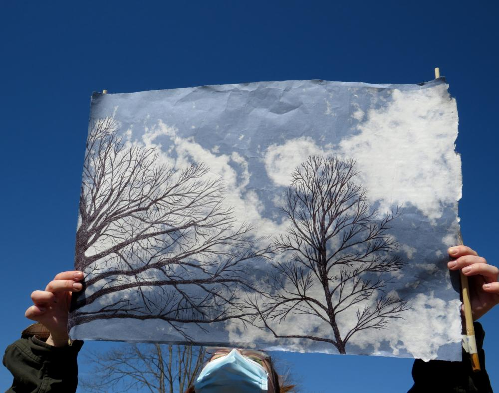A person wearing a mask holds up an image of two black trees. A clear blue sky and a tree can be seen behind the person's head underneath the sheet of paper.