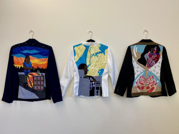 The backs of 3 decorated blazers hung side by side.