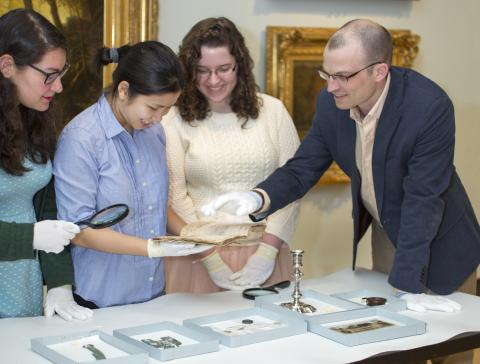 Professor Desmond Fitz-Gibbon and students in the History of Money course examine money-related objects at MHCAM.